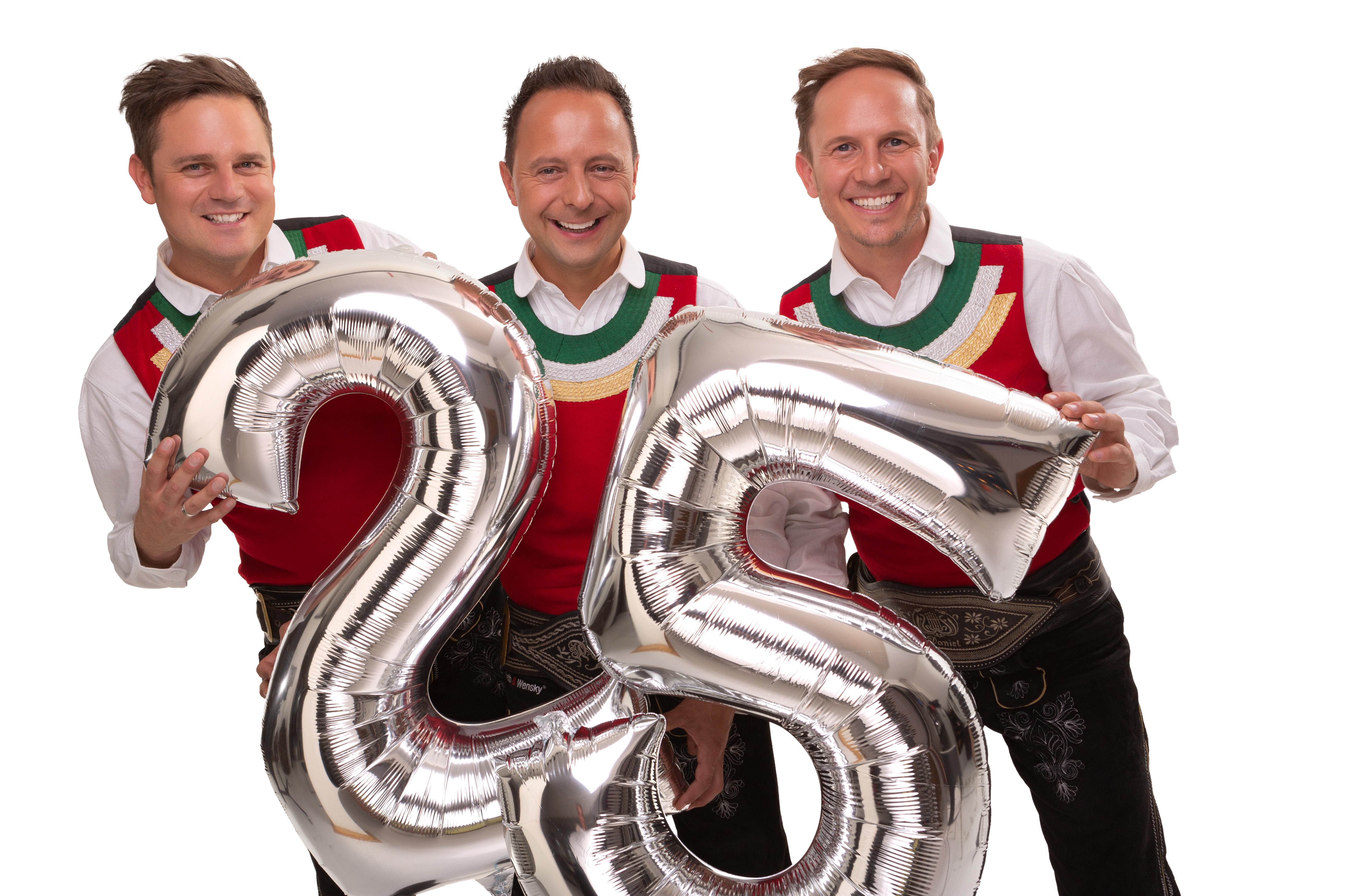 Die jungen Zillertaler feiern Jubiläum, Michael, Markus und Daniel mit einem Luftballon und den Zahlen 2 und 5.